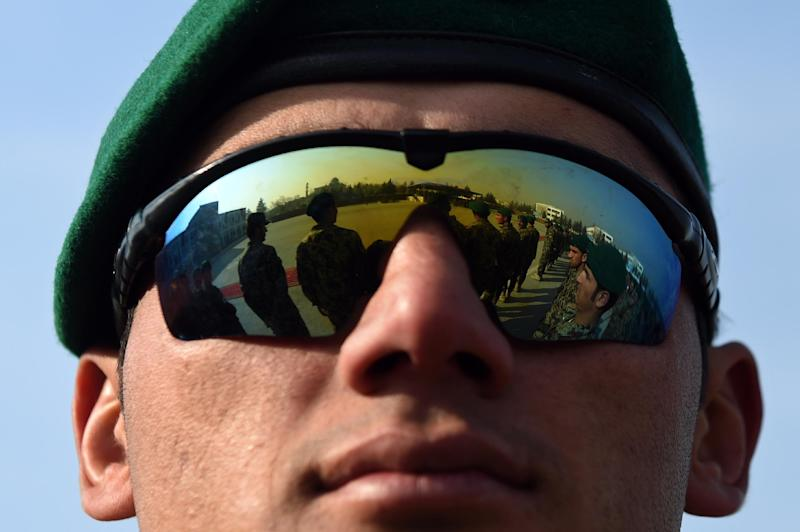 Newly-graduated Afghan National Army cadets are reflected in a pair of comrades sunglasses as they attend their graduation ceremony at the Afghan Kabul Military training centre in Kabul on December 30, 2014