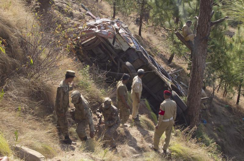 Pakistani army soldiers examine the wreckage of a passenger bus which crashed in Kahuta, near Rawalpindi, Pakistan, Monday, June 4, 2012. The bus carrying a wedding party into a ditch, killing 20 people, a government health official said. (AP Photo/B.K. Bangash)