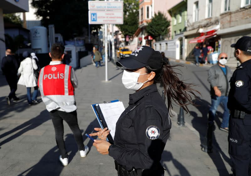 A police officer wearing a protective face mask checks if people wear them in Istanbul