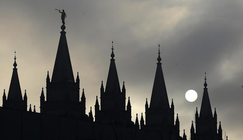 """FILE - In this Feb. 6, 2013, file photo, the angel Moroni statue, silhouetted against a cloud-covered sky, sits atop the Salt Lake Temple in Temple Square in Salt Lake City. A newly-posted article, part of a series of recent online articles posted on the website of The Church of Jesus Christ of Latter-day Saints, affirms the faith's belief that humans can become like God in eternity, but explains that the """"cartoonish image of people receiving their own planets"""" is not how the religion envisions it. (AP Photo/Rick Bowmer, File)"""