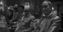 """In this image released by Netflix, Arliss Howard, center, and Charles Dance, right, appear in a scene from """"Mank."""" (Netflix via AP)"""