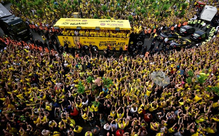 Fans cheer as Borussia Dortmund players arrive at Borsigplatz during celebrations after winning the German Cup final in Dortmund, western Germany (AFP Photo/Sascha Schuermann                   )