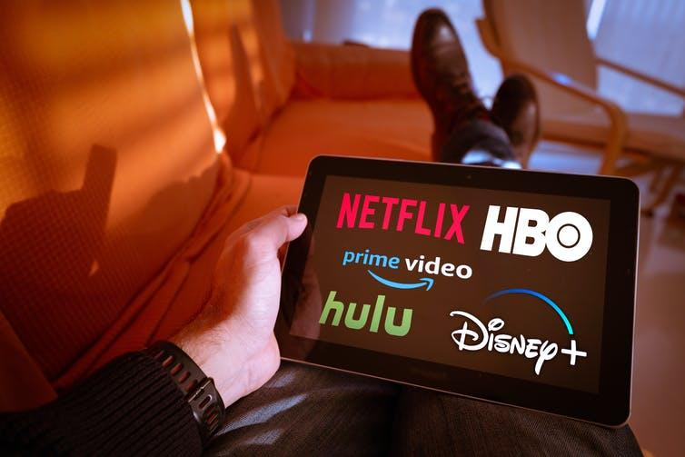 Person holding tablet with Netflix, HBO, Prime video, hulu and Disney+ on the screen