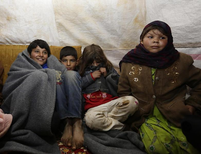 Four of the fourteen children of 60-year old Abu Ali sit covered in blankets to stay warm in a tent at an unofficial refugee camp in al-Saadiyeh, in eastern Bekaa Valley in Lebanon (AFP Photo/Anwar Amro)