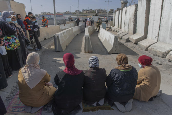 Palestinian women prepare to pray at the Qalandia checkpoint, to protest not allowing them to cross from the West Bank city of Ramallah toward Jerusalem, to attend the first Friday prayers in al-Aqsa mosque, during the Muslim holy month of Ramadan, Friday, April 16, 2021. A limited number of Palestinian residents who carry both a travel permit and a vaccination document, are allowed to cross into Israel to attend the prayers at al-Aqsa mosque, due to the coronavirus pandemic. (AP Photo/Nasser Nasser)