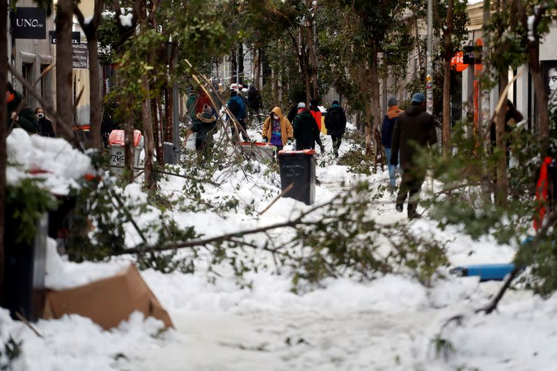 People walk through the snow and among fallen branches in Madrid