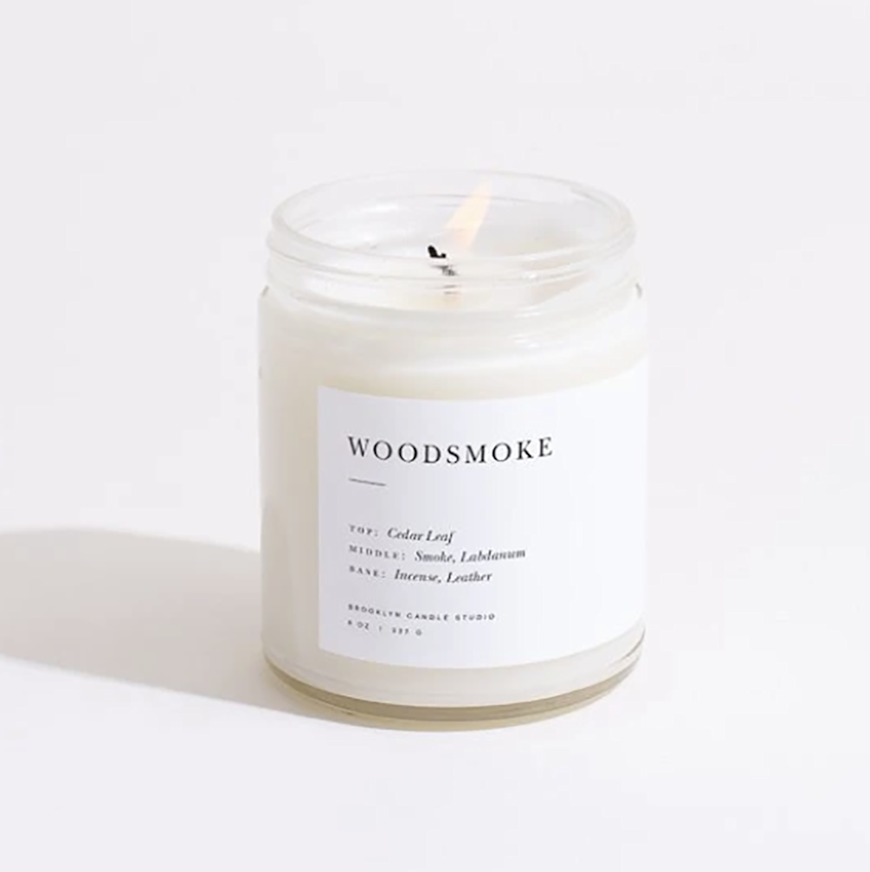 """Well, folks. If you could bottle up autumn and call it a candle, this would be it. What could be better than a candle that smells like crackling fire? With its notes of cedar leaf, labdanum, incense, and a touch of leather, you're bound to feel embraced by a comforting and nostalgic scent that will make you feel like you're camping in the comfort of your bedroom. $24, Brooklyn Candle Studio. <a href=""""https://brooklyncandlestudio.com/collections/shop-all/products/woodsmoke-minimalist-candle"""" rel=""""nofollow noopener"""" target=""""_blank"""" data-ylk=""""slk:Get it now!"""" class=""""link rapid-noclick-resp"""">Get it now!</a>"""