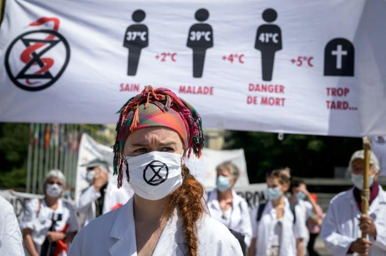 Doctors for Extinction Rebellion protesters march on the World Health Organization's headquarters in Geneva