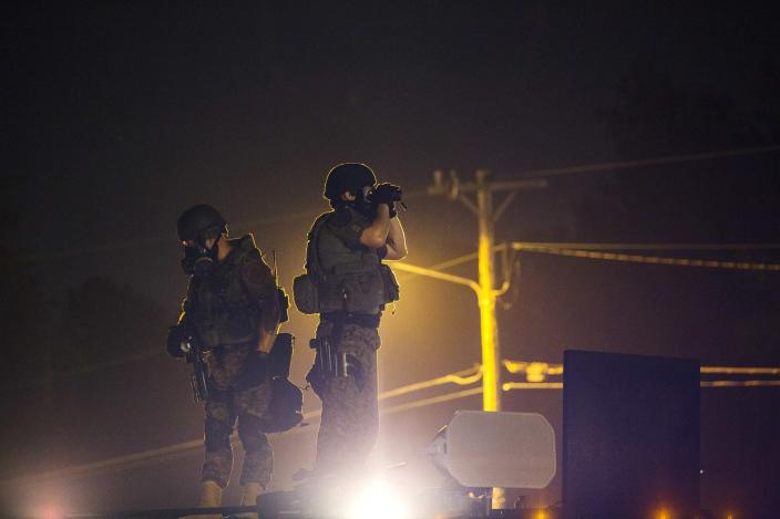 Police officers stand on top of an armored truck to monitor the movements of a rowdy group of demonstrators during protests in reaction to the shooting of Michael Brown near Ferguson, Missouri August 18, 2014. Police fired tear gas and stun grenades at protesters in Ferguson, Missouri on Monday, after days of unrest sparked by the fatal shooting of an unarmed black teenager by a white policeman. REUTERS/Lucas Jackson (UNITED STATES - Tags: CIVIL UNREST CRIME LAW SOCIETY)
