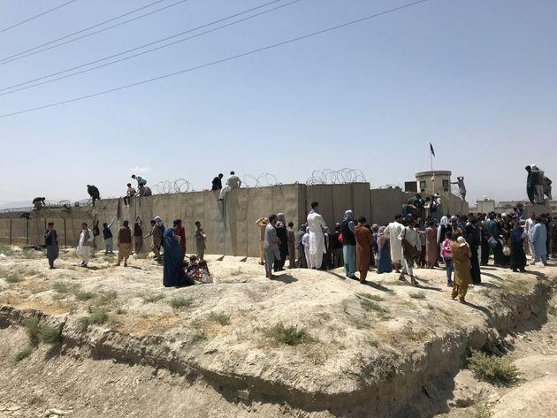 People struggle to cross the boundary wall of Hamid Karzai International Airport to flee the country after rumors that foreign countries are evacuating people even without visas, after the Taliban over run of Kabul, Afghanistan, 16 August 2021.  (Photo by STR/NurPhoto via Getty Images) (Photo: NurPhoto via Getty Images)