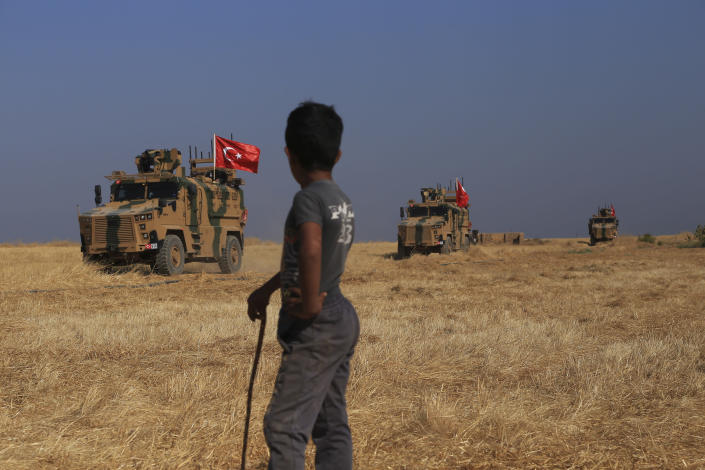 """A Turkish n armored vehicles patrol as they conduct a joint ground patrol with American forces in the so-called """"safe zone"""" on the Syrian side of the border with Turkey, near the town of Tal Abyad, northeastern Syria, Friday, Oct.4, 2019. The patrols are part of a deal reached between Turkey and the United States to ease tensions between the allies over the presence of U.S.-backed Syrian Kurdish fighters in the area. (AP Photo/Baderkhan Ahmad)"""