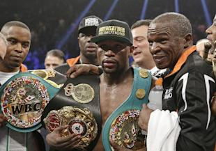 Floyd Mayweather Jr. poses with his champion's belts and his father Floyd Mayweather Sr. (AP)
