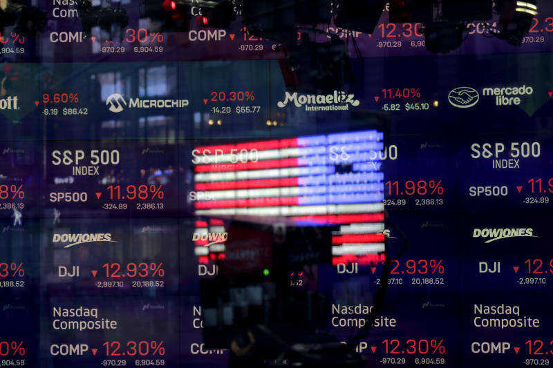 FILE - In this March 16, 2020, file photo, United States flag is reflected in the window of the Nasdaq studio, which displays indices and stocks down, in Times Square, New York. (AP Photo/Seth Wenig, File)