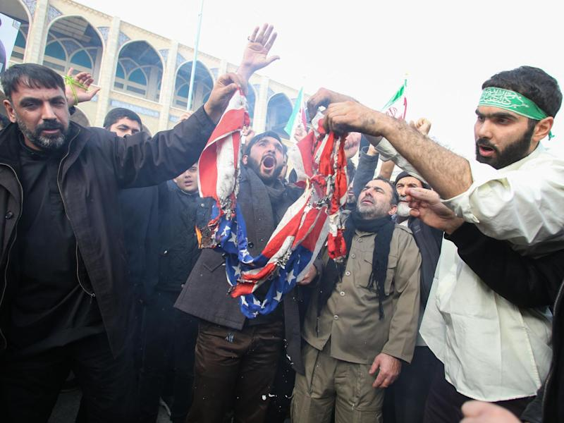 """Iranians burn a US flag during a demonstration against American """"crimes"""" in Tehran on 3 January, 2020 following the killing of Iranian Revolutionary Guards Major General Qasem Soleimani in a US strike on his convoy at Baghdad international airport: (2020 Getty Images)"""