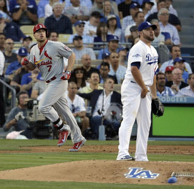 St. Louis Cardinals' Matt Holliday watches his two-run home run off Los Angeles Dodgers starting pitcher Ricky Nolasco during the third inning of Game 4 of the National League baseball championship series Tuesday, Oct. 15, 2013, in Los Angeles. (AP Photo/Chris Carlson)