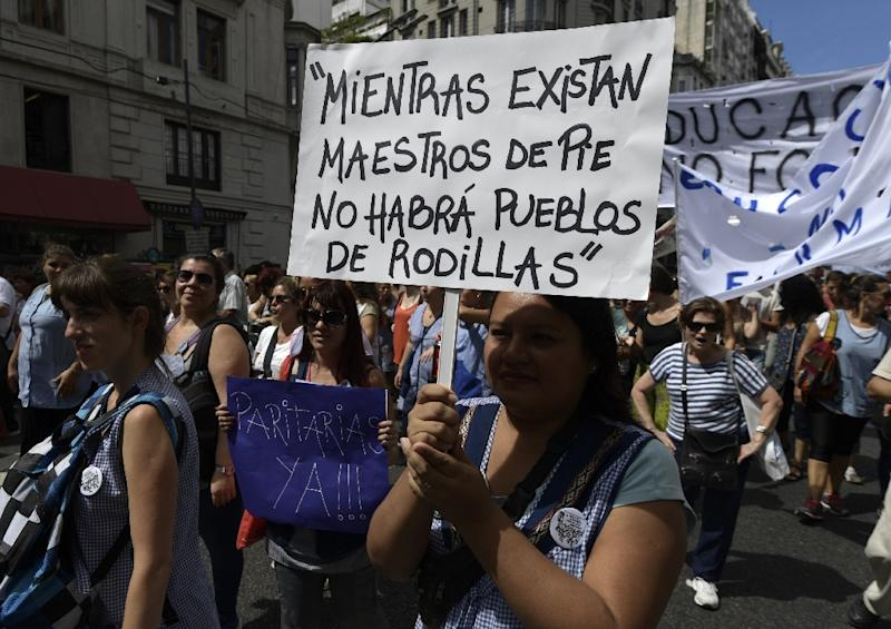 "A teacher holds a placard reading ""While there are teachers standing, there will be no people on their knees"" during a 48-hour nationwide strike demanding pay rises, in Buenos Aires on March 6, 2017"