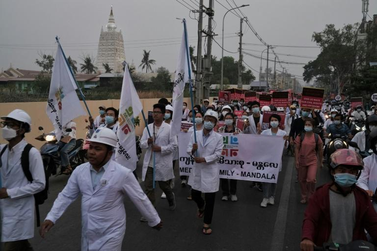 Myanmar medical personnel take part in a dawn protest against the military coup in Mandalay