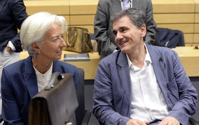 Greek Finance Minister Euclid Tsakalotos (R) speaks with Managing Director of the International Monetary Fund (IMF) Christine Lagarde during a meeting of the Eurogroup finance ministers in Brussels on July 12, 2015 (AFP Photo/John MacDougall)
