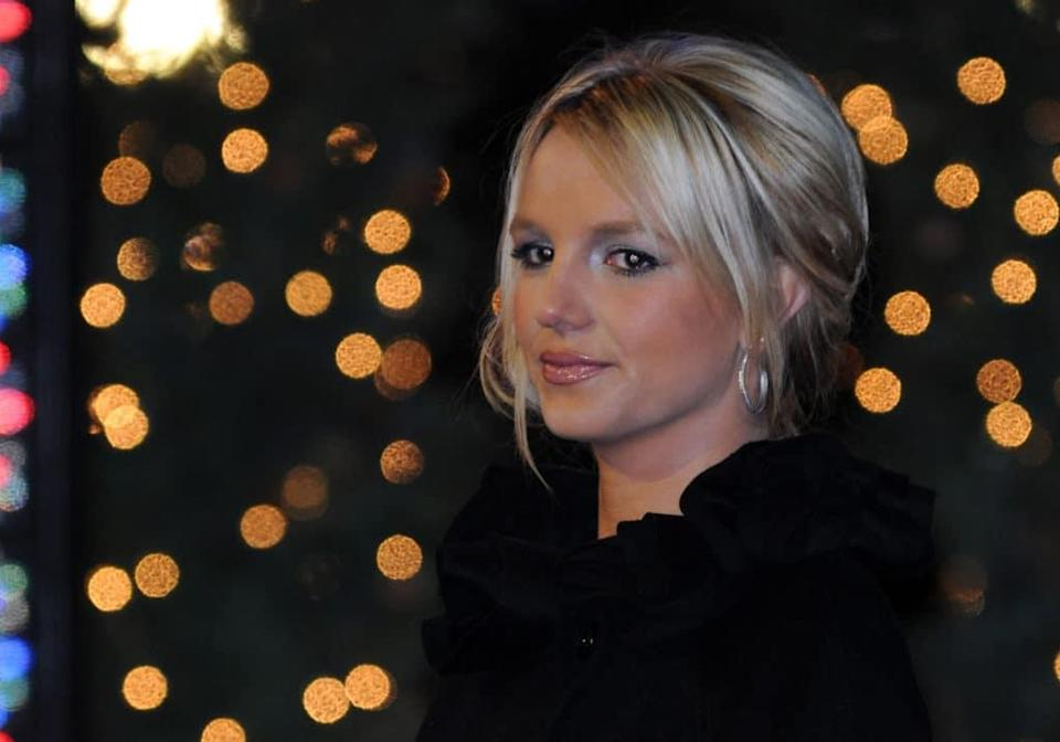 Britney Spears faintly smiles against a backdrop of blurred-out lights