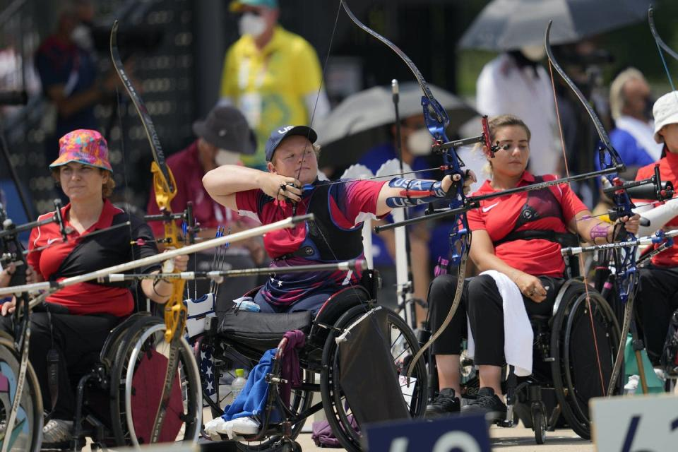 Wheelchair para-archery athletes pulling the string back on their bows