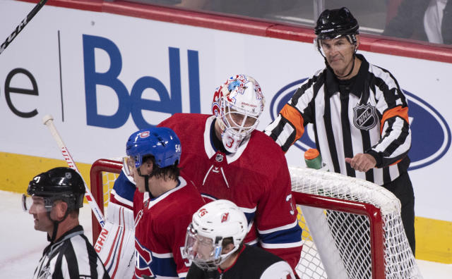 In this photo taken Sept. 17, 2018, referee Wes McCauley, right, keeps an eye on the play as the Montreal Canadiens face the New Jersey Devils during third-period preseason NHL hockey game action in Montreal. An informal poll of NHL players leaves no doubt as to who the most popular referee is: Veteran McCauley. (Paul Chiasson/The Canadian Press via AP)