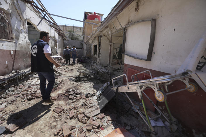 A man walks through a heavily damaged hospital in the city of Afrin, Syria, Sunday, June 13, 2021. Shells have hit the hosptal Saturday, killing at least 13 people, including two medical staff and two ambulance drivers. It was not immediately clear who was behind the shelling, which came from areas where government troops and Kurdish-led fighters are deployed. (AP Photo/Ghaith Alsayed)