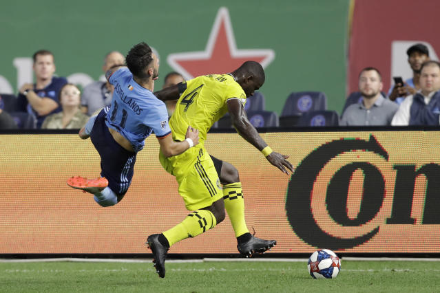 Columbus Crew defender Jonathan Mensah (4) sends New York City FC midfielder Valentin Castellanos (11) flying during the first half of an MLS soccer match, Wednesday, Aug. 21, 2019, in New York. (AP Photo/Kathy Willens)