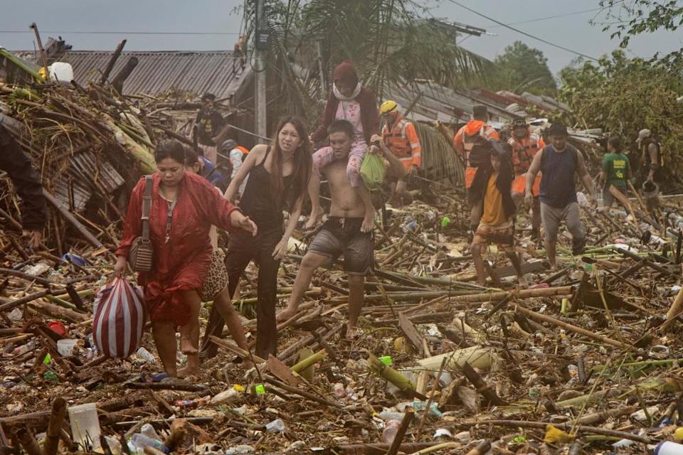 Residents walk across debris floating in floodwaters in a submerged village, as Typhoon Vamco hits in Rodriguez, Rizal province, Philippines.