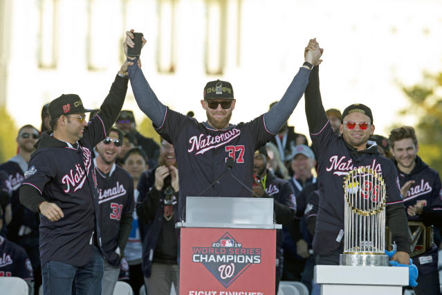 FILE - In this Nov. 2, 2019, file photo, Washington Nationals pitcher and World Series MVP Stephen Strasburg, center, celebrates the World Series baseball championship during a rally following a parade to celebrate the team's World Series baseball championship over Houston Astros, in Washington. Nationals right fielder Gerardo Parra is right and pitcher Anibal Sanchez, left. World Series MVP Stephen Strasburg is staying with the Washington Nationals. The right-hander has agreed to a record $245 million, seven-year contract, a person familiar with the negotiations told The Associated Press on Monday, Dec. 9, 2019. The person spoke on condition of anonymity at baseball's annual winter meetings because the agreement had not been announced. (AP Photo/Jose Luis Magana, File)