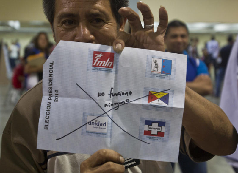 An election officer shows a ballot while counting votes at a polling station in San Salvador, El Salvador, Sunday, Feb. 2, 2014. Presidential elections in two Central American countries are both referendums on political stagnation, with voters in Costa Rica deciding whether to oust the long-ruling party, and voters in El Salvador deciding whether to bring it back to power. (AP Photo/Esteban Felix)