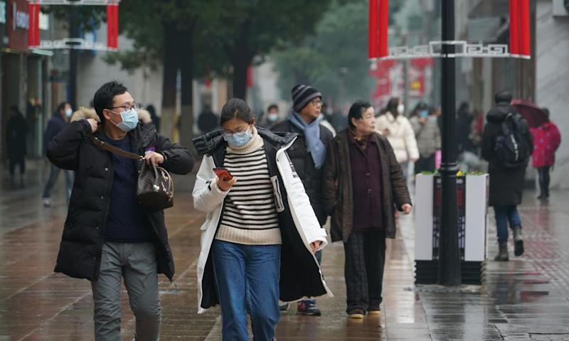 Masked pedestrians in downtown Wuhan, China, the city where the outbreak originated.