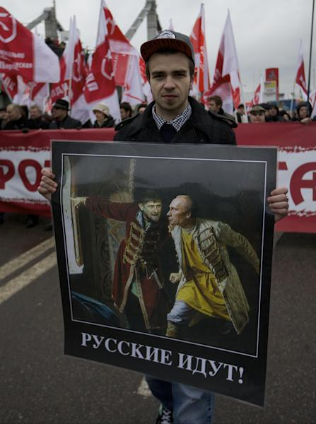 """A man carries a picture depicting President Vladimir Putin, right, and his relations with Chechen local President Ramzan Kadyrov, and criticizing his policy on Chechnya, with the caption reading """"Russians are coming!"""", as he and other nationalist demonstrators and activists march to mark National Unity Day, in Moscow, on Sunday, Nov. 4, 2012. The march took place on Unity Day, a national holiday established in 2005 to replace commemorations of Bolshevik Revolution. (AP Photo/Ivan Sekretarev)"""