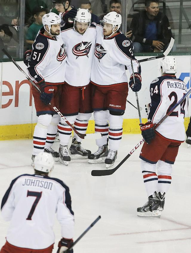 Columbus Blue Jackets forward Artem Anisimov (42) is congratulated by teammates Fedor Tyutin (51), Jack Skille (5), Derek MacKenzie (24) and Jack Johnson (7) after scoring a goal against the Dallas Stars during the first period of an NHL hockey game on Wednesday, April 9, 2014, in Dallas. (AP Photo/Brandon Wade)