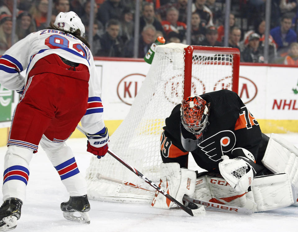 The shot on goal by New York Rangers' Mika Zibanejad, left, is stopped by Philadelphia Flyers' Carter Hart during the first period of an NHL hockey game, Monday, Dec. 23, 2019, in Philadelphia. (AP Photo/Tom Mihalek)