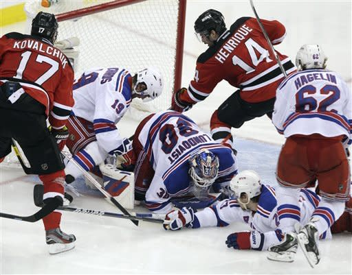 New Jersey Devils' Adam Henrique (14) scores against New York Rangers goalie Henrik Lundqvist, of Sweden, in overtime of Game 6 of the NHL hockey Stanley Cup Eastern Conference finals, Friday, May 25, 2012, in Newark, N.J. The Devils won 3-2 to advance to the Stanley Cup finals. (AP Photo/Frank Franklin II)