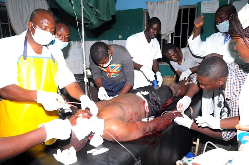 Health workers treat a bomb blast victim in the Nigerian city of Jos on December 11, 2014