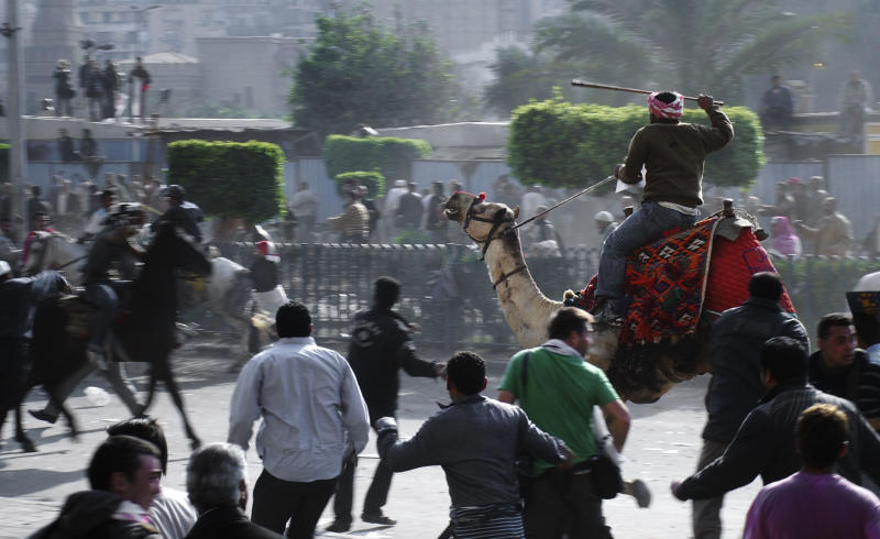 FILE - In this Wednesday, Feb. 2, 2011 file photo, supporters of President Hosni Mubarak, riding camels and horses, fight with anti-Mubarak protesters in Cairo, Egypt. Egypt's highest appeals court has upheld the acquittal on Tuesday, May 8, 2013 of 24 loyalists of ousted President Hosni Mubarak tried for organizing the 'Battle of the Camel,' an attack on protesters that was a pivotal moment in the country's 2011 uprising.(AP Photo/Mohammed Abu Zaid, File)