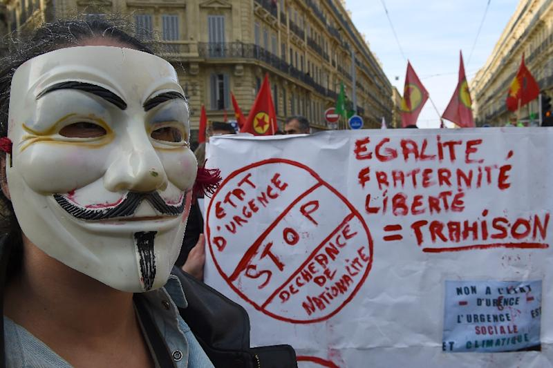 "A person wearing a Guy Fawkes mask stands next to a banner reading ""Stop the state of emergency and the loss of nationality"" during a demonstration in Marseille, southern France, on January 30, 2016 (AFP Photo/Boris Horvat)"