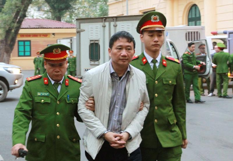 Vietnamese former state oil executive Trinh Xuan Thanh (C) is led toward a courtroom for the verdict in his trial at Hanoi's People's Court (AFP Photo/Vietnam News Agency)