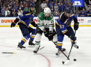 St. Louis Blues' Alex Pietrangelo (27) drops his broken stick as David Perron (57) attempts to control a loose puck in front of Dallas Stars' Jason Dickinson (16) during the second overtime period in Game 7 of an NHL second-round hockey playoff series, Tuesday, May 7, 2019, in St. Louis. (AP Photo/Jeff Roberson)