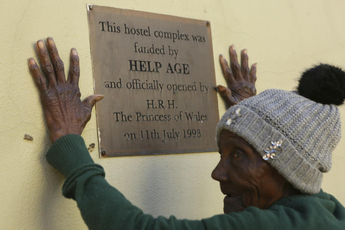 An elderly person stands near a placard at the Society for the Destitute Aged care home in Harare's Highfield township, Zimbabwe, Saturday June, 26, 2021. Princess Diana officially opened an accommodation wing at the home amid much fanfare in 1993. The economic ravages of COVID-19 are forcing some families in Zimbabwe to abandon the age old tradition of taking care of the elderly. Zimbabwe's care homes have experienced a 60% increase in admissions since the outbreak of the pandemic in March last year. (AP Photo/Tsvangirayi Mukwazhi)