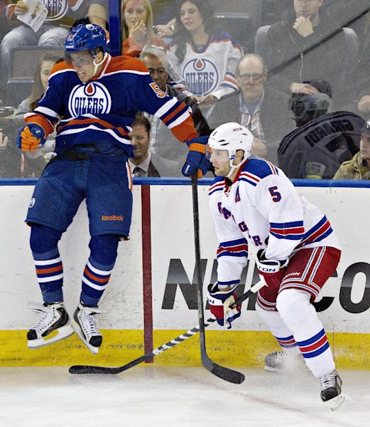 New York Rangers' Dan Girardi (5) dodges a check from Edmonton Oilers' David Perron (57) during the first period of an NHL hockey preseason game, Tuesday, Sept. 24, 2013, in Edmonton, Alberta. (AP Photo/The Canadian Press, Jason Franson)