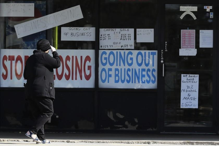 A woman looks at signs at a store in Niles, Ill., on May 13.