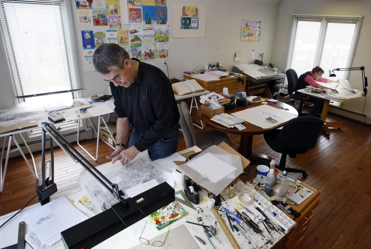 In this Jan. 25, 2011 photo, as his mother, Janice Berenstain, works in the background, Mike Berenstain looks through sheets of artwork for a Berenstain Bears book in the studio that they share in Solebury, Pa. It used to be husband and wife Jan and Stan Berenstain creating the books, but their son Mike took over when his father died, continuing the tradition that started with the first book in 1962.