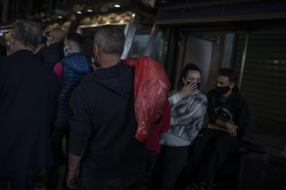 A consumer wearing protective face mask carries a lamb at the main meat market of Athens during Orthodox Holy Week, Thursday, April 29, 2021. (AP Photo/Petros Giannakouris)