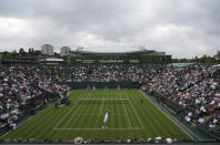 Argentina's Federico Delbonis serves to Russia's Andrey Rublev during the men's singles match on day one of the Wimbledon Tennis Championships in London, Monday June 28, 2021. (AP Photo/Alberto Pezzali)