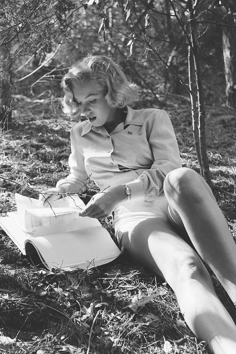 <p>Marilyn Monroe reading during a photo shoot at Griffith Park in Los Angeles in August. Her shirt's embroidered with her initials, MM. </p>