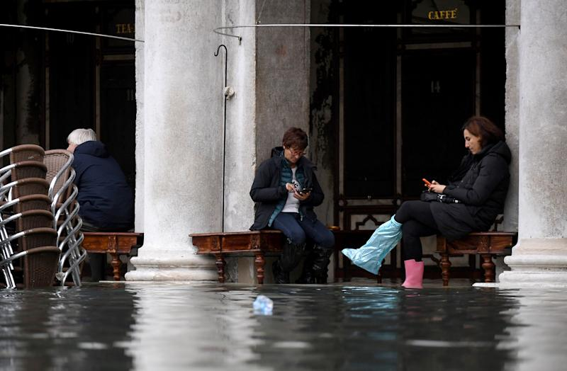 People sit outside a cafe under arcades at St. Mark's Square during high tide in Venice, Italy, on Nov. 17, 2019.  (Photo: Alberto Lingria / Reuters)