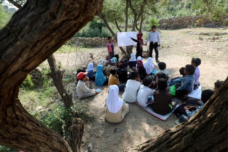 Twenty Yemeni pupils listen to their teacher with textbooks balanced in their laps as they sit under trees in their southern village, where the school building remains unfinished