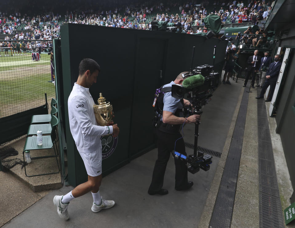 Serbia's Novak Djokovic holds his winner's trophy and leaves the court after the presentation ceremony for the men's singles final on day thirteen of the Wimbledon Tennis Championships in London, Sunday, July 11, 2021. (Steve Paston/Pool Via AP)